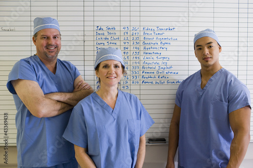 Doctors standing next to schedule whiteboard in hospital