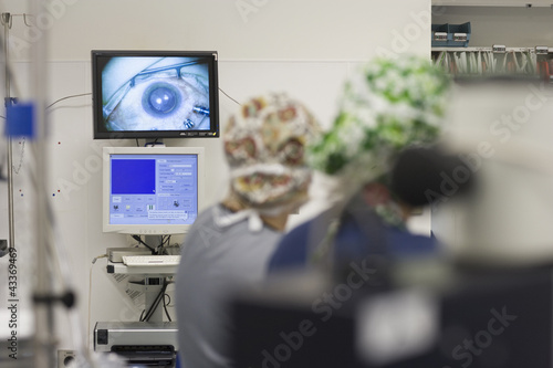 Doctors performing microsurgery in operating room