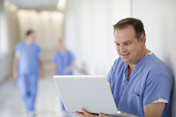 Caucasian doctor using laptop in hospital corridor