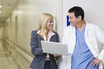 Businesswoman showing laptop to doctor in hospital corridor