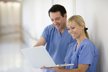 Doctors looking at laptop in hospital corridor