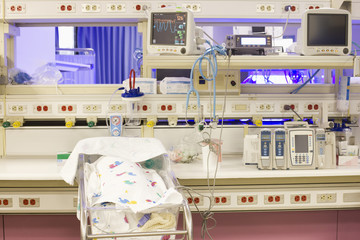 Baby in warming bassinet in hospital