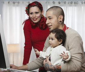 Alternative Hispanic parents using computer with young daughter