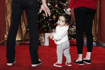 Hispanic parents holding baby daughter's hands near Christmas tree