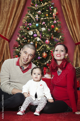 Hispanic family sitting in front of Christmas tree