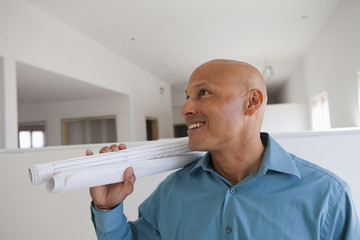 Hispanic architect holding blueprints in unfinished room