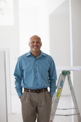 Hispanic architect standing in unfinished room