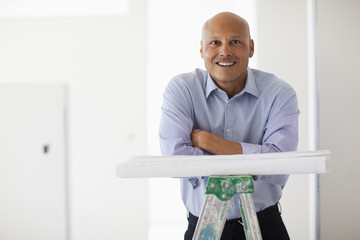 Hispanic architect with blueprints in unfinished room