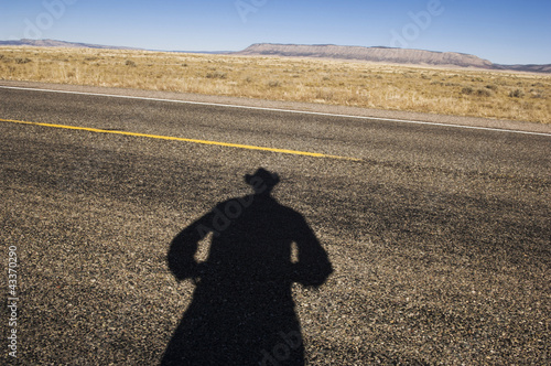 Shadow of cowboy on remote highway