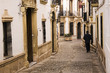 Man walking down cobblestone alley in quaint village