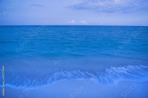 Waves on beach of tranquil blue ocean