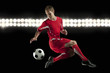 Soccer player jumping in mid-air kicking ball at night