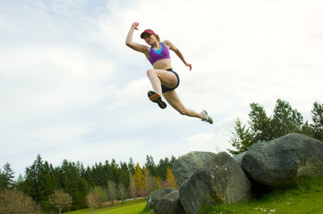Mixed race teenager jumping from rock
