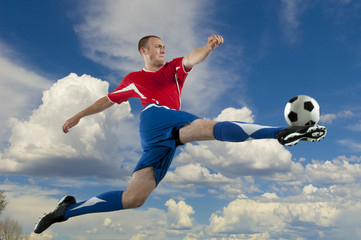 Caucasian soccer player jumping in mid-air kicking ball