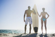 Mixed race couple standing on beach with surfboard