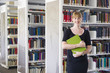 Caucasian student holding book in library