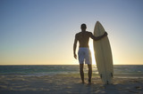 Mixed race man standing on beach with surfboard