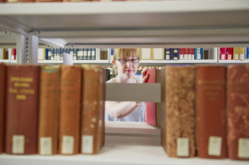 Caucasian woman taking book from shelf in library