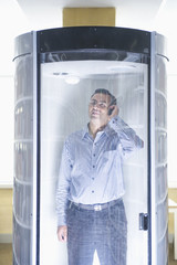 Indian man using cell phone in isolation booth