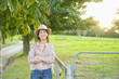 Smiling Hispanic woman standing near fence