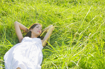 Hispanic woman sleeping in grass