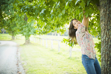 Hispanic woman climbing tree