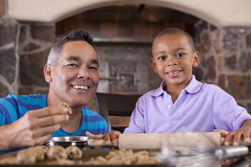 Mixed race father and son baking cookies together