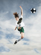 Caucasian teenager kicking soccer ball in mid-air