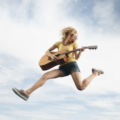 Caucasian woman jumping in mid-air playing guitar