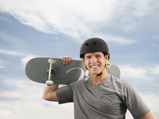 Caucasian man holding skateboard