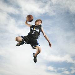Caucasian teenager playing basketball