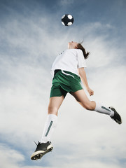 Caucasian teenager heading soccer ball in mid-air
