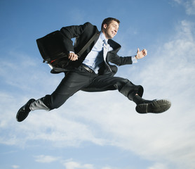 Caucasian businessman jumping in air