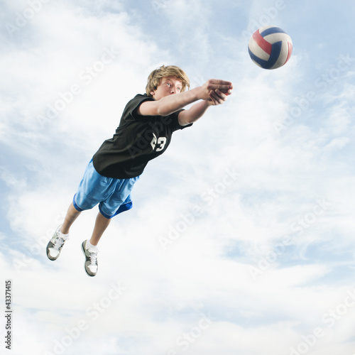 Caucasian teenager returning volleyball