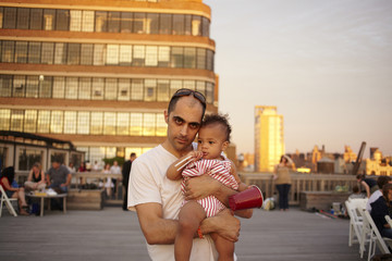 Father holding baby daughter on urban deck