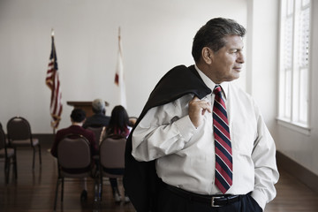 Hispanic businessman standing in meeting room