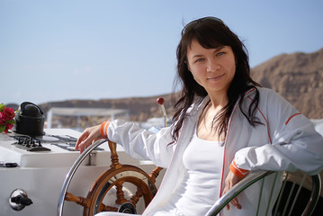 girl sits at the helm of the ship