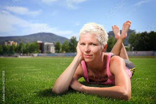 Active woman lying on green grass