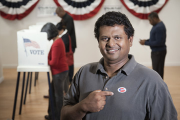 Man pointing to I Voted sticker