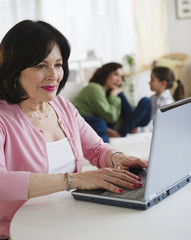 Woman using laptop with family in background