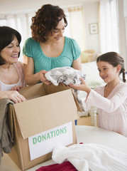 Family packing box of clothing donations
