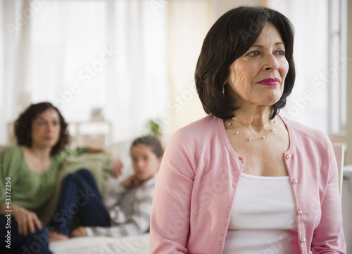 Serious woman with family in background