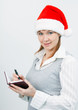 woman with a notebook in a Christmas hat