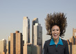 Mixed race businesswoman flipping hair in urban environment