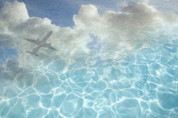 Clouds and airplane reflected in swimming pool water