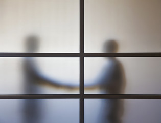 Businessmen shaking hands behind glass wall in office