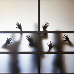 Business people pressing hands against glass wall in office