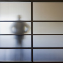 Businessman standing behind glass wall