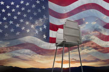 Sunset and American flag behind voting booth
