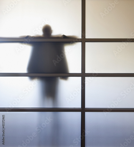 Businessman standing behind glass wall in office